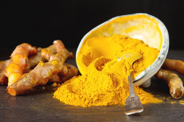 fresh turmeric with a bowl of powdered turmeric
