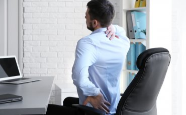 man with sore back, bad posture, office pain, ergonomic nightmare